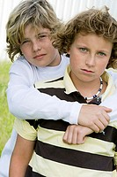 Portrait of a boy hugging another boy from behind (thumbnail)