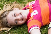 Portrait of a girl lying on the grass and smiling (thumbnail)