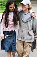 Close-up of a girl and a boy walking with their arms around each other