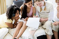 High angle view of a girl writing on a notepad with her friends sitting beside her
