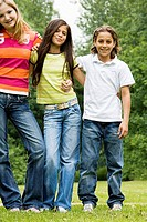 Portrait of two girls and a boy standing in a park with their arms around each other