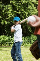 Two children playing baseball in a park