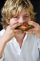 Portrait of a boy eating a sandwich