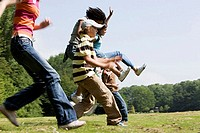 Side profile of five children running in a park