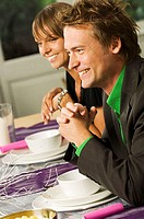 Side profile of a mid adult man with a young woman smiling at a dining table