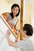 Side profile of a mid adult man using a hammer with a young woman helping him