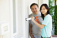 Mid adult man standing with a young woman using a caulk gun