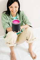 High angle view of a young woman holding a paint can