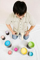 High angle view of a young man holding a paint roller with paint cans in front of him