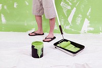 Low section view of a man standing with a paint roller