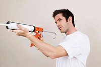Side profile of a young man holding a caulk gun