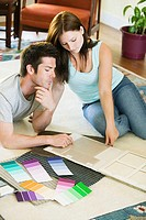High angle view of a young couple with color swatches in front of them