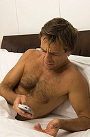 Close-up of a young man operating a mobile phone in the bed (thumbnail)