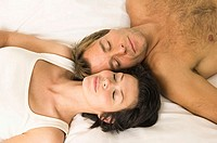Close-up of a young couple sleeping in bed