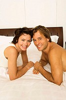 Portrait of a young couple lying in the bed and smiling