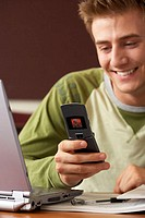Close-up of a college student using a mobile phone and smiling