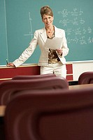 Portrait of a professor standing in front of a blackboard and holding a paper