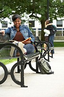 Portrait of a college student sitting on a bench and smiling