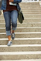 Low section view of a college student moving down a staircase and carrying books