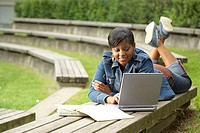 College student lying on a bench and using a laptop