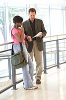 Side profile of a college student standing with her professor in a corridor