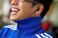 Close-up of a college student wearing headphones and listening to music