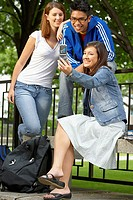 Three college students taking their picture with a mobile phone
