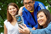 Close-up of three college students taking their picture with a mobile phone
