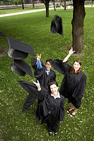 Portrait of two female graduates and a male graduate throwing their mortarboards in the air