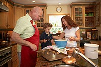 Boy standing with his grandparents in the kitchen