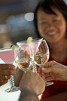 Human hands toasting with glasses and a mature woman smiling in the background