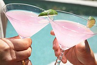 Close-up of two people's hands toasting with martini glasses