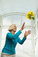 Senior woman catching bunch of flowers, smiling, low angle view