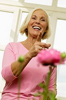 Senior woman laughing, low angle view, portrait