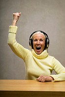 Senior woman wearing headphones, laughing, close-up