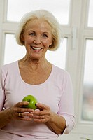 Senior woman holding apple, smiling, close-up, portrait