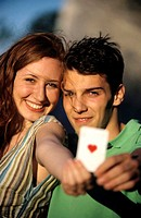 Young couple showing ace of hearts, focus on couple at background, close-up