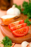 Sliced tomato, onion, garlic and parsley on chopping board
