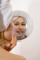 Young woman applying face mask, looking into mirror, smiling, close-up