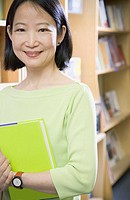 Middle-aged Asian woman holding book
