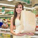 Woman holding paper grocery bag at supermarket, Perth, Australia