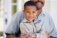 African American boy sitting on father´s lap