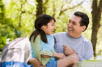 Hispanic father and daughter laughing outdoors