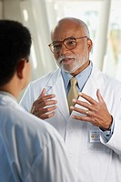 Middle-aged African doctor talking to co-worker