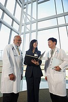 Businesswoman talking to two male doctors, North Bethesda, Maryland, United States