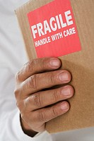 Close up of male hand holding package with fragile sticker