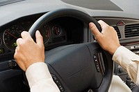 Close up of man's hands on steering wheel