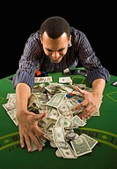 Studio shot of man raking pile of money off gambling table