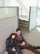 Male and female coworkers on floor leaning on office cubicle wall