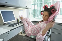 Hispanic woman in pajamas and curlers sleeping at her desk, Redwood City, California, United States